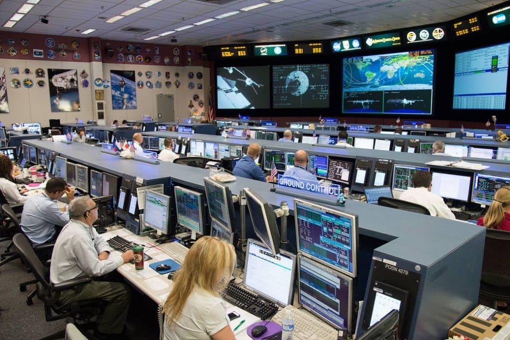El Centro de Control de la Misión en el Centro Espacial Johnson de la NASA con empleados federales y contratistas en el trabajo.